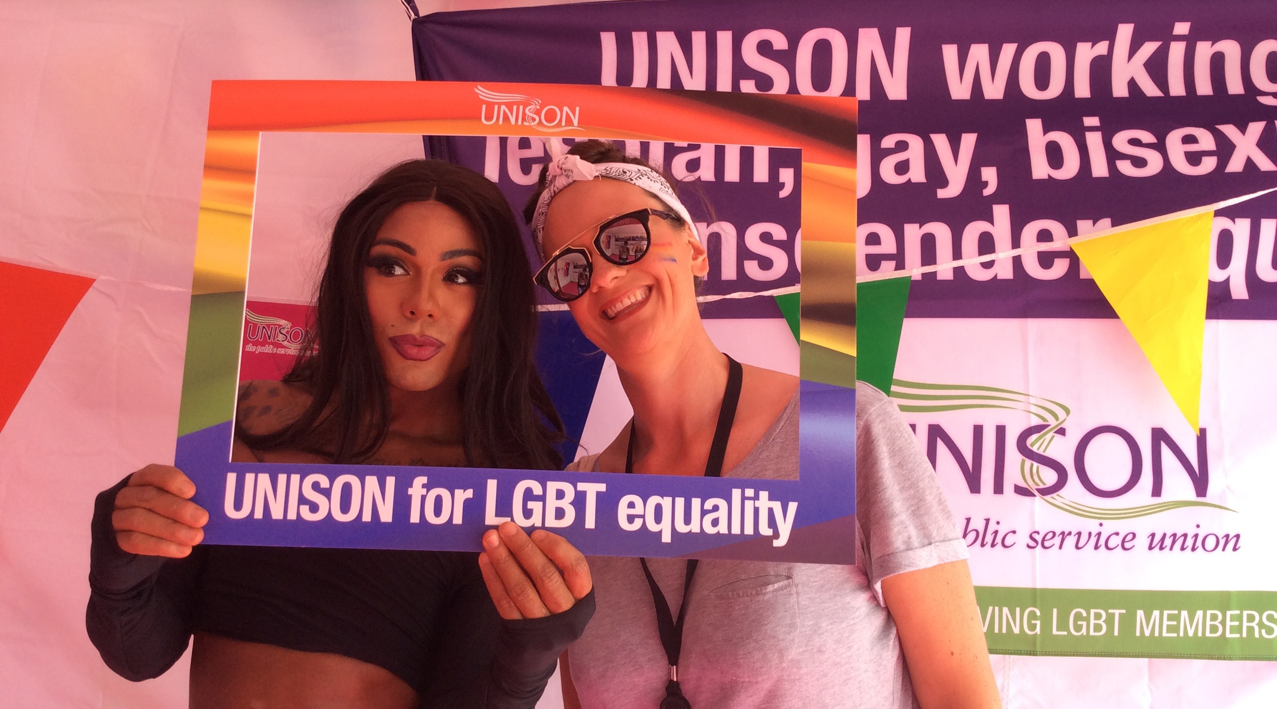 Two people put their heads through a UNISON LGBT+ frame