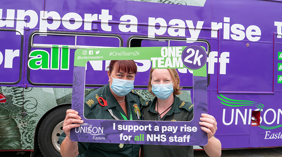 Two female ambulance workers hold a selfie frame supporting an NHS pay rise with a bus also supporting an NHS pay rise in the background