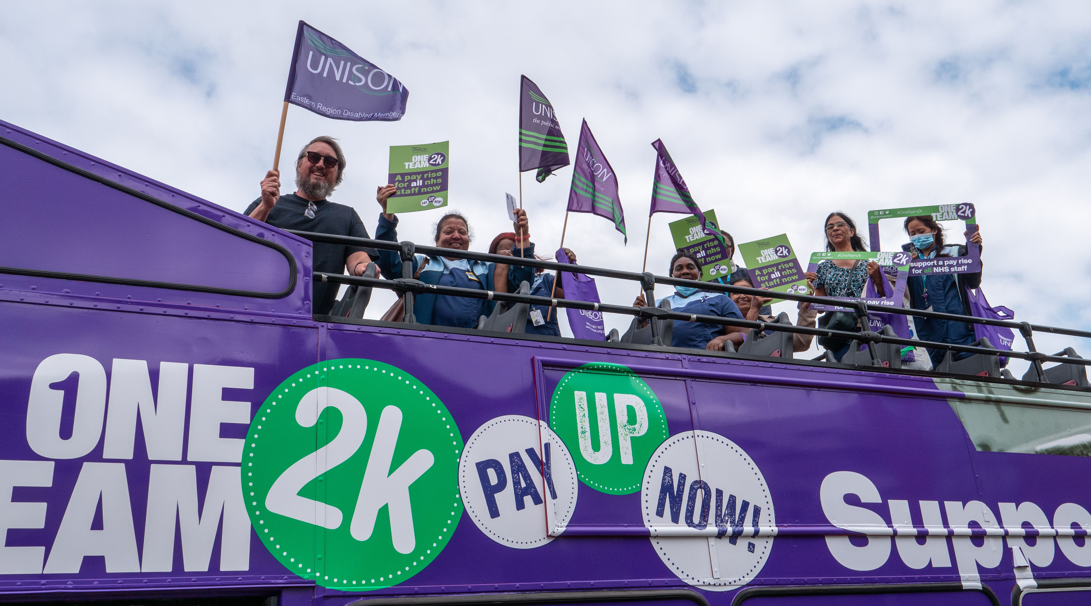 NHS workers on an open-top pay bus holding flags and calling for a pay rise