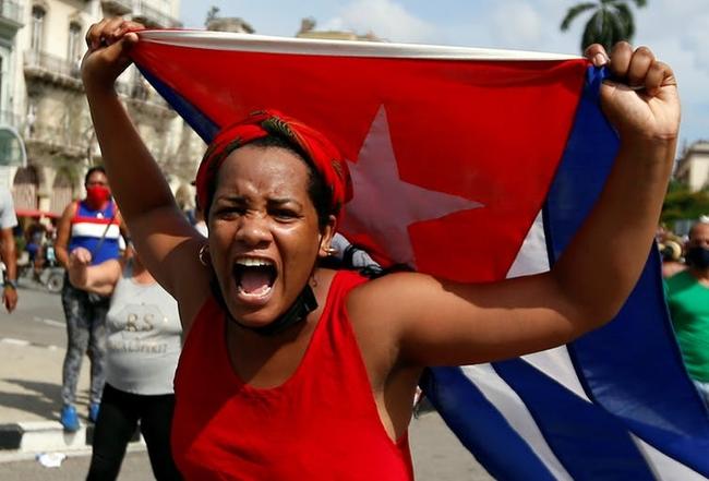 A woman holds the Cuban flag