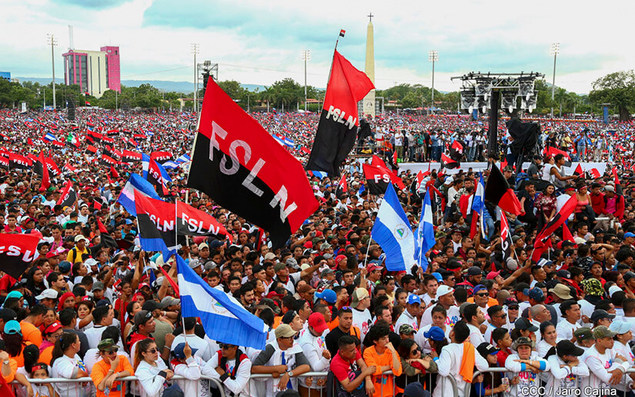 A large demonstration with people waving Nicaraguan and FSLN flags